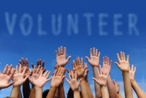 Image of hands in the air with the word Volunteer above