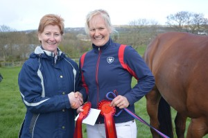 Lisa Boyle 85cm class winner receiving prize money and rosette from Norma Wilkinson  repesenting The Lodge Hotel class sponsor